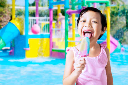 licking tongue: Attractive little girl wearing swimsuit while standing at the pool and eating ice cream