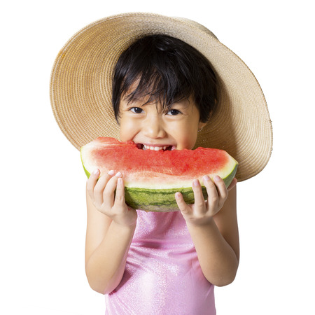 asian bikini: Closeup of cute little girl standing in the studio while eating a fresh watermelon and wearing hat Stock Photo