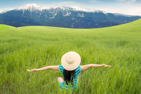 fresh women: Back view of happy woman with hat sitting on the green meadow while enjoying fresh air Stock Photo