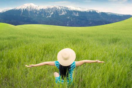 aire puro: Volver la vista de mujer feliz con sombrero sentado en el prado verde mientras disfruta del aire fresco Foto de archivo