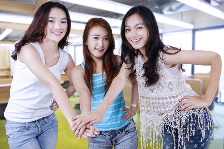 joining hands: Three young female students standing in the classroom and joining hands together Stock Photo