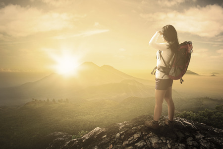 adventure holiday: Rear view of young woman standing on the mountain peak while carrying backpack and enjoying sunrise view Stock Photo