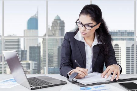 papeles oficina: Empresario indio joven que trabaja en la oficina con ordenador port�til mientras escribe en el libro