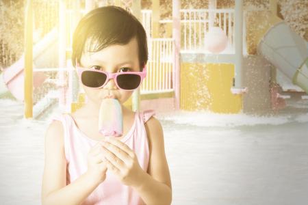 petite fille maillot de bain: Portrait de petite fille heureuse debout au bord de la piscine, tout en portant des lunettes de soleil et profiter de la cr�me glac�e