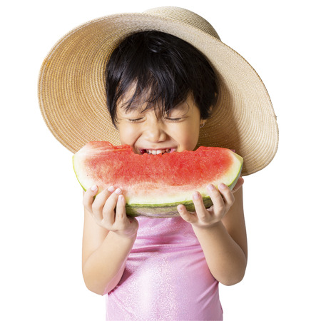 Attractive little girl wearing a big hat while eating watermelon in the studio, isolated on white