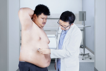 Doctor is checking a fat man. shoot in the hospital photo