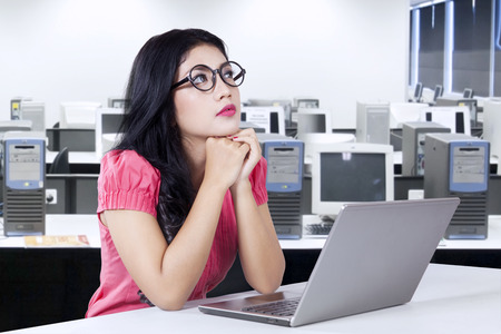 woman looking up: Portrait of female worker sitting in the office with laptop computer on the table and looks thinking something