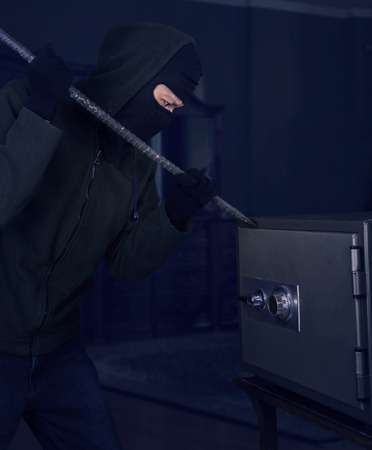 thievery: A burglar with a crowbar is trying to open a safe at home