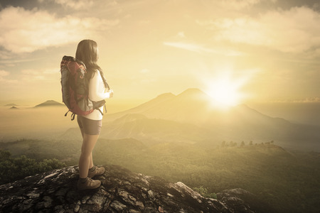 valley view: Rear view of female backpacker standing on the mountainside while carrying backpack and enjoying valley view Stock Photo