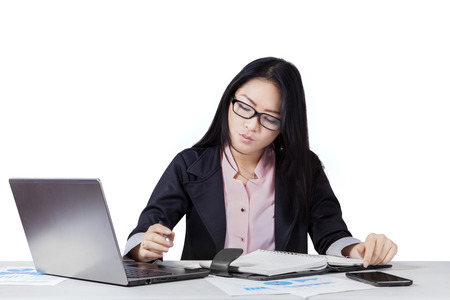 working papers: Chinese businesswoman working with laptop and notebook on desk, isolated on white background Stock Photo