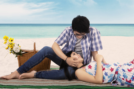 caress: Portrait of happy couple relaxing at the beach with the man caress his girlfriend