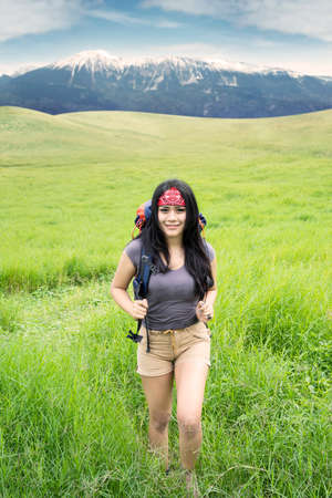 Portrait of beautiful woman smiling on the camera while carrying rucksack for hiking, shot on the hill photo