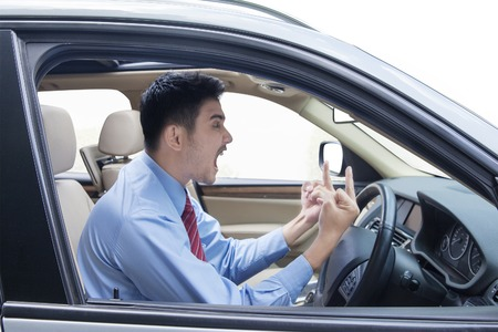 yell: Portrait of young entrepreneur looks angry in the car while showing two middle fingers and shouting