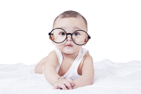 Retrato del pequeño bebé mirando a la cámara mientras está acostado en la cama y llevaba unas gafas redondas