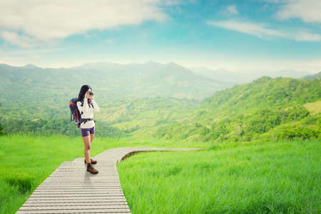nature photo: Female backpacker standing on the wooden path while carrying backpack and taking picture with digital camera Stock Photo