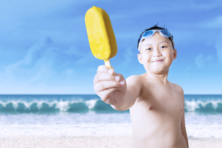 child ice cream: Portrait of attractive male kid, showing a delicious ice cream on the camera, shot at the beach
