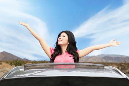sunroof: Portrait of happy woman enjoying freedom on the sunroof of new car