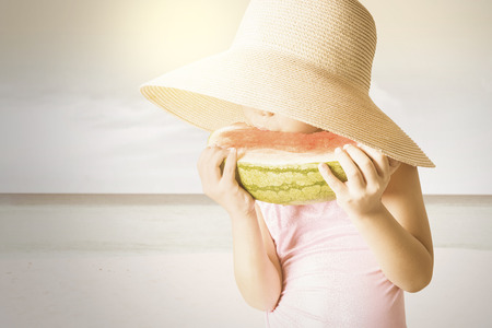 children swimsuit: Portrait of little child wearing a big hat on the seaside and eating a fresh watermelon Stock Photo