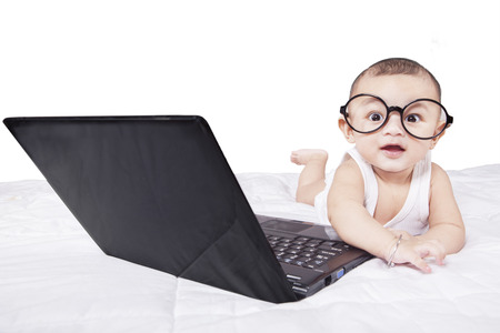 Portrait of funny baby wearing round glasses, lying on bed with laptop computer, isolated on white Stock Photo