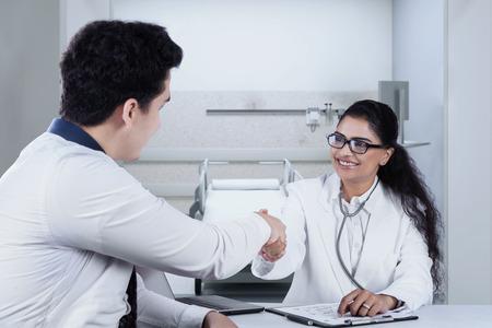 manos estrechadas: Vista trasera de apretones de manos de los pacientes masculinos con su m�dico despu�s de chequeo en el hospital Foto de archivo