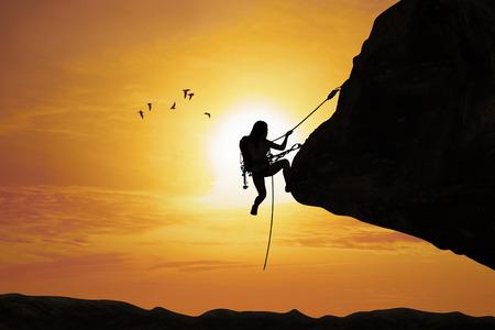 escalada: Silueta de las mujeres j�venes tratan de subir a la monta�a en la puesta del sol Foto de archivo