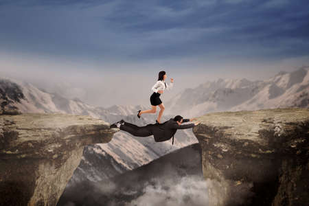 business obstacle: Businesswoman trust on her friend to help she through the cliff as the business obstacle