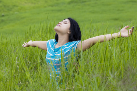 Beautiful young woman with casual clothes enjoying freedom while breathe fresh air and outstretched hands on the meadow Stock Photo