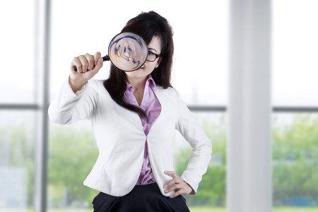 investigating: Young businesswoman looking at the camera through a magnifier in the office