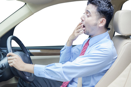 Portrait of young entrepreneur driving a car while yawning and looks tired, isolated on white