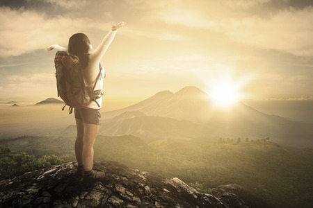 Rear view of female backpacker carrying backpack and stretch her hands on the mountain photo