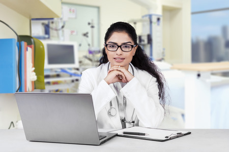 asian medical: Portrait of young indian doctor sitting in the hospital and looking at the camera Stock Photo