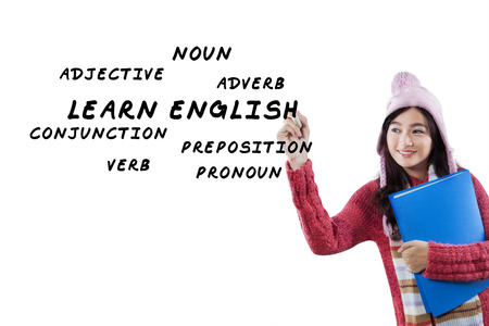 language school: Young asian student in winter clothes learns English and write English material on whiteboard