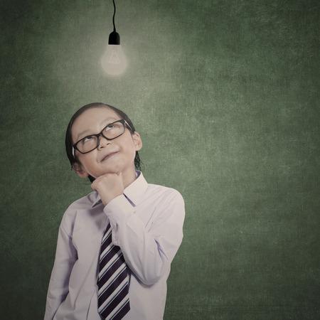 niños actuando: Poco pensamiento empresario bajo bombilla encendida en la clase