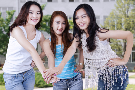 joining hands: Three happy female students standing at schoolyard while joining hands together