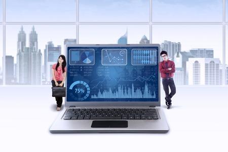 jovenes empresarios: Dos j�venes emprendedores de vacas flacas en la computadora port�til con la carta financiera crecen hacia arriba Foto de archivo
