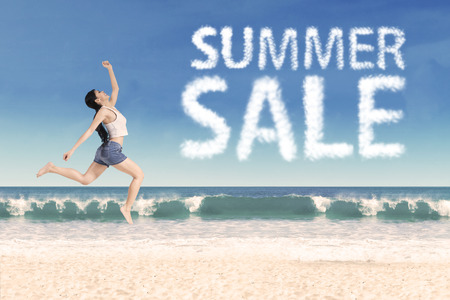 whitehaven: Summer sale clouds and woman jumping at beach Stock Photo