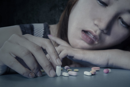 illicit: Stressful young girl using narcotic shaped pills, shot at home