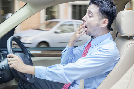 Portrait of businessman driving a car while yawning, shot on the road