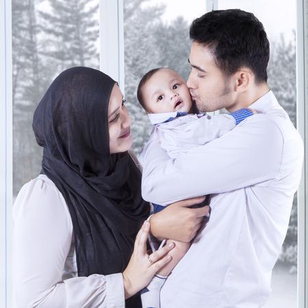femmes muslim: Portrait d'heureux parents �treignant leur petit b�b� � la maison, abattu avec un fond d'hiver sur la fen�tre Banque d'images