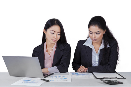 mixed race people: Portrait of two asian businesswomen working on desk with financial chart and laptop Stock Photo
