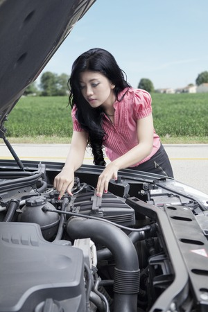 Portrait of a pretty woman checking a broken car alone on the road
