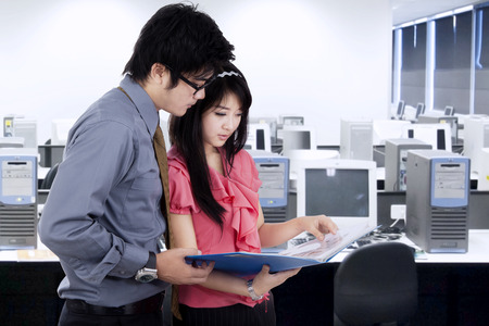 Portrait of two businesspeople discussing business document in office photo
