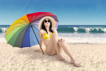 Portrait of beautiful woman wearing swimwear sitting on sand under a rainbow umbrella at coast