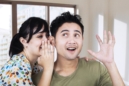 couple talking: Asian girl spreads the good news to her boyfriend Stock Photo