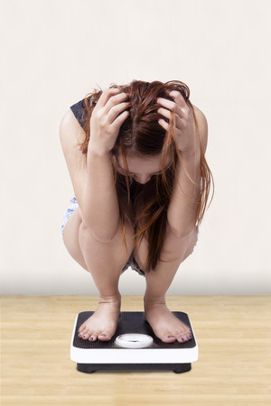 lose weight: Teenage girl looks stressed when measure her weight on a weight scales at home
