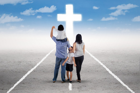 jesus in heaven: Back view of little happy family standing on the road and follow a cross Stock Photo