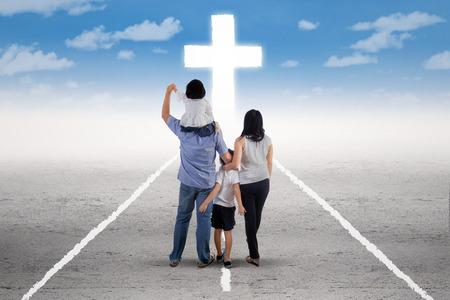 familia cristiana: Vista trasera de la pequeña familia feliz que se coloca en la carretera y seguir una cruz