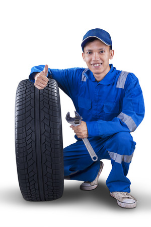 tire repair shop: Male mechanic with a tire smiling at the camera while showing thumb up and holding a wrench