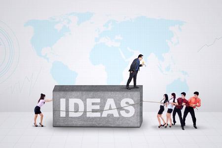 jonge ondernemers: Groep van jonge ondernemers proberen om een steen te verplaatsen met een tekst van ideeën