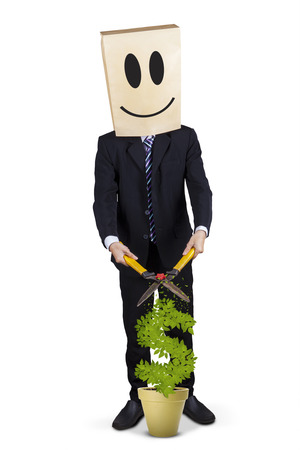 Businessman with cardboard head and smiley icon, using scissors to cut money tree photo